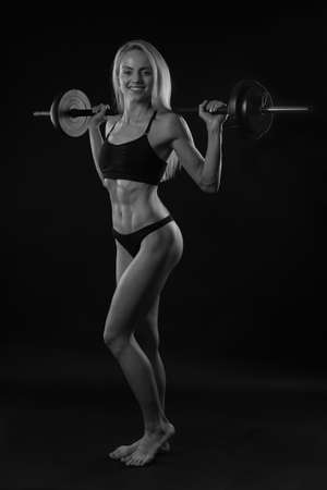 darck: Muscular Girl with a barbell on darck background