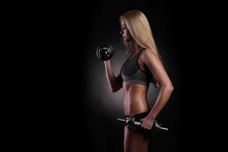 beautiful sporty muscular woman working out with dumbbells photo