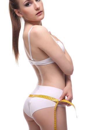 elasticidad: young woman measuring waist on blue background Foto de archivo