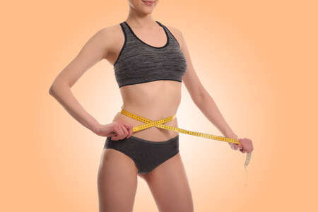 fatness: young woman measuring waist. Healthy lifestyle, losing weight