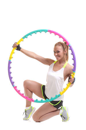 young sporty woman with hula hoop on a white background