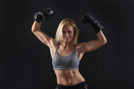 Girl in boxing gloves on a black background