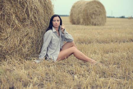 Schöne Frau sitzt im Feld mit Heuhaufen Standard-Bild - 82869762