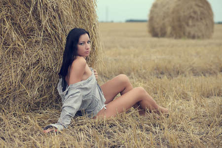 beautiful woman sitting in field with haystacks Banque d'images