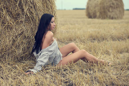 beautiful woman sitting in field with haystacks Stock Photo