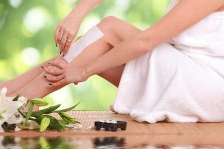 Une photo d'une jeune femme en train de cirer ses jambes Banque d'images - 88609765