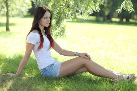Sexy erotic girl with mini skirt on green grass Stok Fotoğraf - 100752994