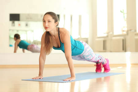 Young strong fitness athletic girl doing push-ups Foto de archivo