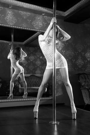Female striptease on the pole in a nightclub