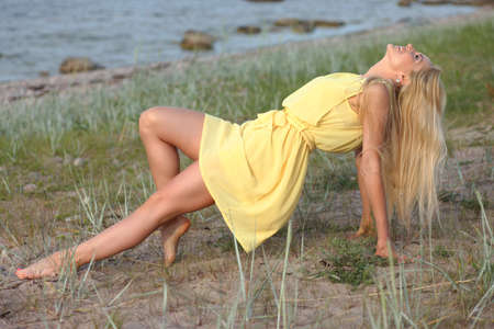 Beautiful blonde girl in a yellow dress on the beach Banque d'images