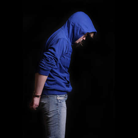 Young arrested criminal in handcuffs on a black background Foto de archivo
