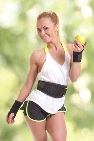 Beauty young sporty woman holding apple