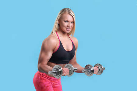 sexy young muscular woman posing with dumbbells Stock Photo