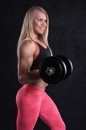 sexy young muscular woman posing with dumbbells Imagens