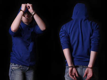 Young arrested criminal in handcuffs on a black background Zdjęcie Seryjne