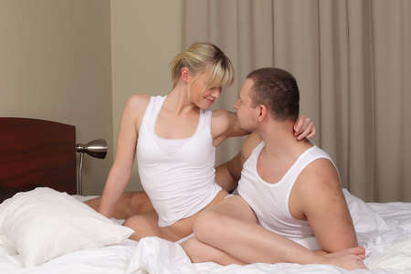 young couple in bed, man and woman on white blanket Stock Photo