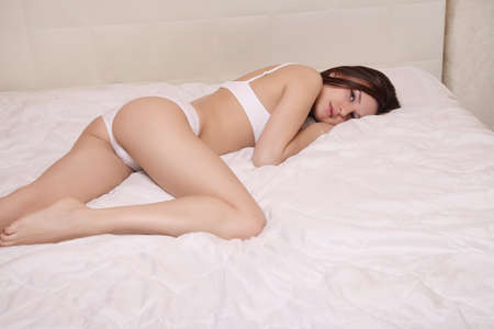 Portrait of a beautiful girl lying on a white bed Stock Photo