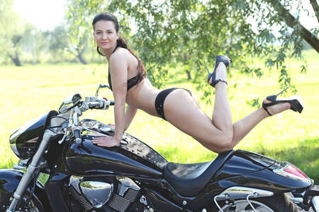 Portrait of a young woman in a black bikini on motobike