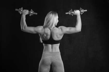 Young sporty slim muscular girl with dumbbells