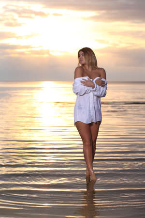 summer fashion photography with pretty woman in the water at sunset