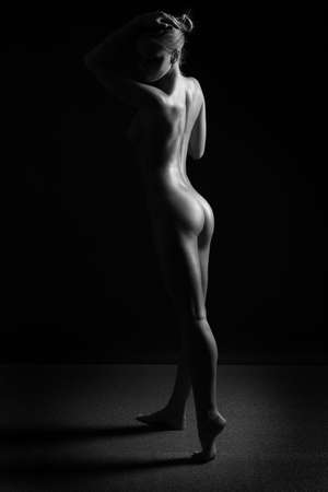 young beautiful female body on a dark background