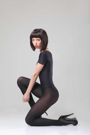 Bellissima modella in posa in studio su sfondo grigio