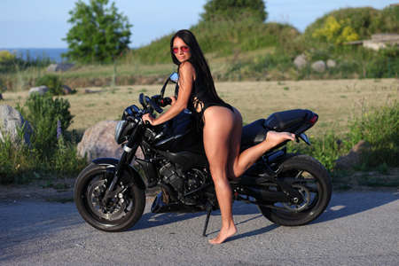 young sexy girl in swimsuit posing with motorcycle