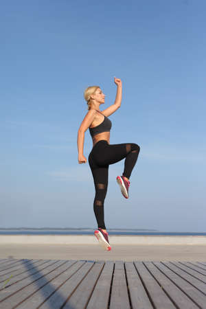Fitness female woman with muscular body jumping