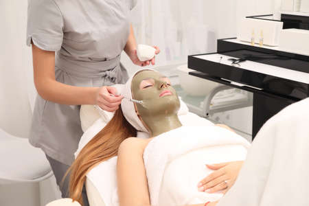facial treatment of young woman in a cosmetology salon