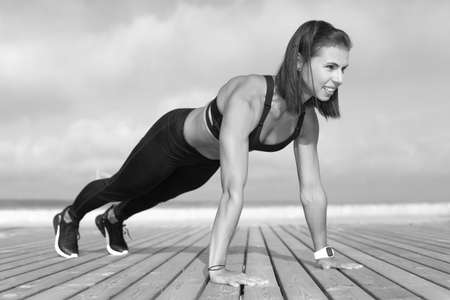 Young strong athletic girl holds a workout