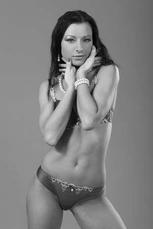 young slim sexy girl posing on gray background Standard-Bild
