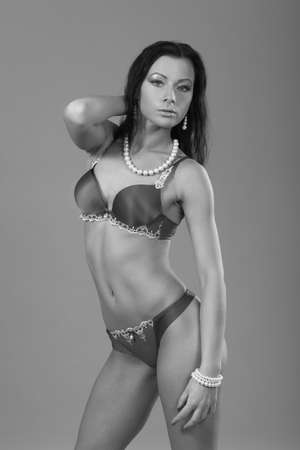 young slim sexy girl posing on gray background Banco de Imagens