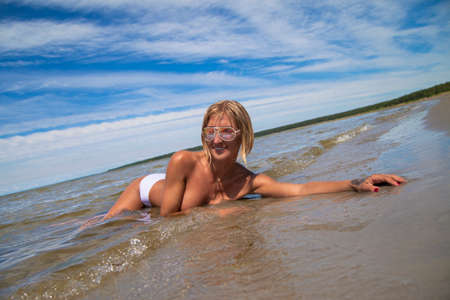 young woman with big on a sandy beach Imagens