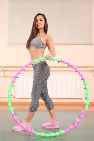beautiful young girl doing sports with a hoop