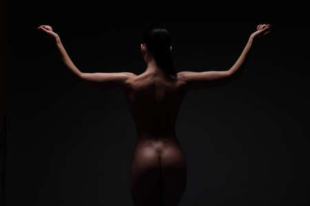 young woman back and butts on a black background