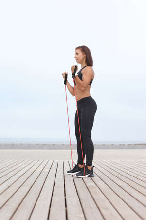 Brunette woman doing exercises with rubber band, fitness outdoor