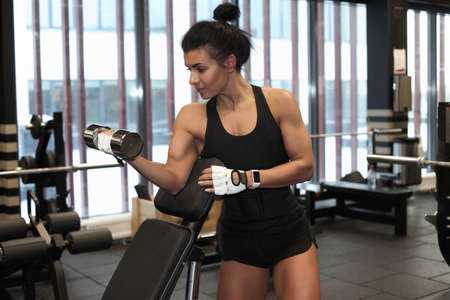 Fitness woman model performing weight lifting exercise at gym