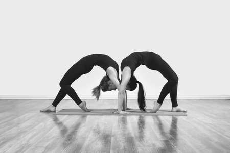 Two slim girls are doing yoga indoors