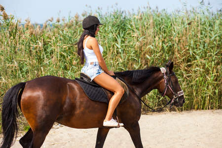 young girl riding a horse on the beach