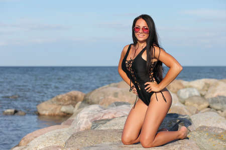 young beautiful girl on a stone in a black swimsuit