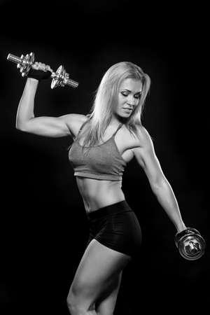 Atletische jonge vrouw die training met gewichten op donkere achtergrond doet Stockfoto