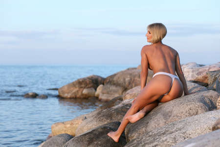 young naked athletic girl on the stone by the sea Фото со стока