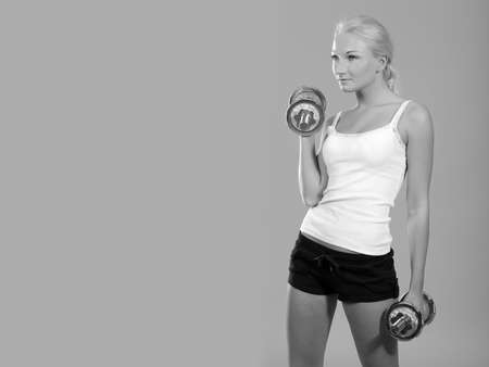fitness woman in sportswear doing exercises with dumbells.
