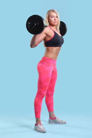 Fitness young girl doing exercises on a blue background Imagens
