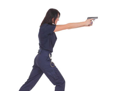young woman police officer with a pistol on a white background