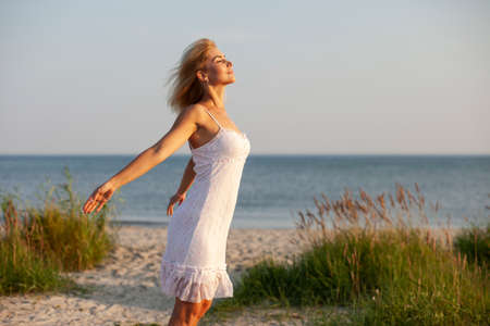 happy woman walking on the beach at sunset