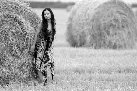 young beautiful free woman in a field with hay