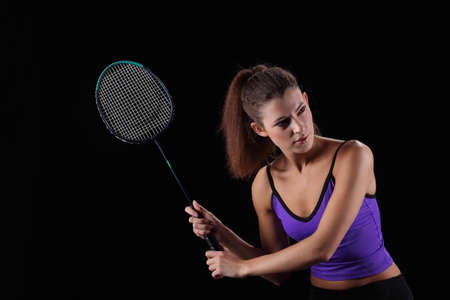 A young girl with a rocket plays badminton
