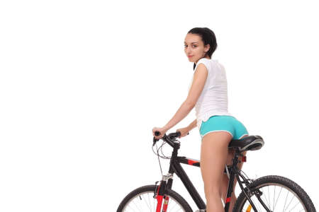Sexy fitness.Young seductive woman in sport wear posing on the bicycle