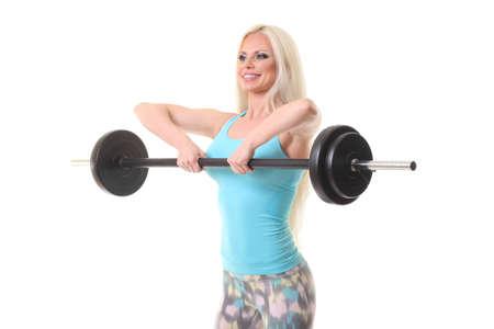 Sonriente mujer deportiva haciendo ejercicio con barra sobre un fondo blanco. Foto de archivo
